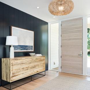 ミネアポリスの片開きドアビーチスタイルのおしゃれな玄関 (黒い壁、淡色無垢フローリング、淡色木目調のドア、ベージュの床) の写真