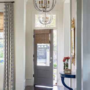 Entryway - transitional dark wood floor, brown floor and tray ceiling entryway idea in Charleston with white walls and a gray front door