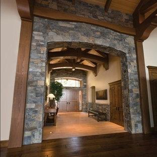 На фото: огромные входные двери в классическом стиле с коричневыми стенами, темным паркетным полом, двустворчатой входной дверью, входной дверью из дерева среднего тона и коричневым полом