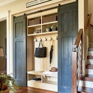 Diseño de vestíbulo posterior rústico con paredes beige y suelo de madera en tonos medios