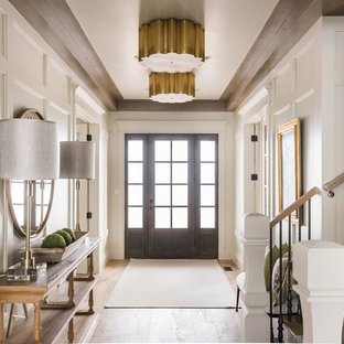Exemple d'un hall d'entrée chic de taille moyenne avec un mur blanc, un sol en bois clair, une porte simple, une porte en verre et un sol beige.
