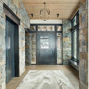 他の地域の広い回転式ドアラスティックスタイルのおしゃれな玄関ドア (グレーの壁、金属製ドア、茶色い床、無垢フローリング) の写真