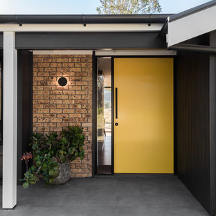 This is an example of a mid-sized midcentury front door in Other with grey walls, slate floors, a single front door, a yellow front door and grey floor.