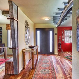 Cette photo montre une grand entrée éclectique en bois avec un couloir, un sol en bois brun, une porte simple, un sol multicolore et un mur beige.