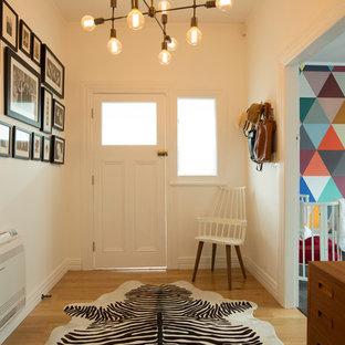 Exempel på en mellanstor industriell ingång och ytterdörr, med vita väggar, ljust trägolv, en enkeldörr och en vit dörr