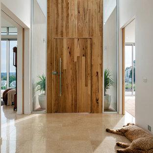 Rustik inredning av en mellanstor entré, med vita väggar, en enkeldörr, mellanmörk trädörr och travertin golv