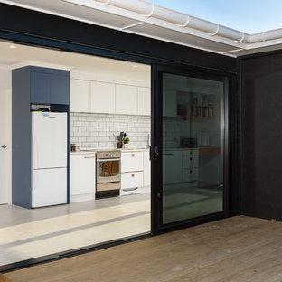 Imagen de puerta principal marinera con paredes negras, suelo de madera en tonos medios, puerta corredera, puerta negra y suelo blanco