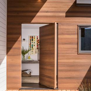 Diseño de puerta principal contemporánea con puerta de madera en tonos medios y puerta pivotante