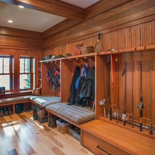 Example of a large mountain style light wood floor and brown floor mudroom design in New York with brown walls