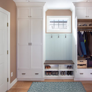 Small transitional medium tone wood floor and blue floor mudroom photo in New York with brown walls and a white front door