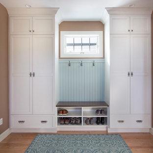 Ejemplo de vestíbulo posterior tradicional renovado, pequeño, con paredes marrones, suelo de madera en tonos medios, puerta blanca y suelo azul