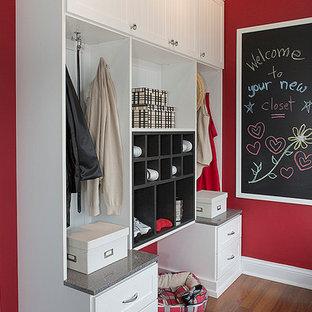 Cette image montre une entrée traditionnelle de taille moyenne avec un vestiaire, un mur rouge et un sol en bois brun.