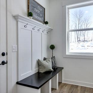 ミネアポリスの中くらいの片開きドアカントリー風おしゃれなマッドルーム (白い壁、ラミネートの床、白いドア、グレーの床) の写真