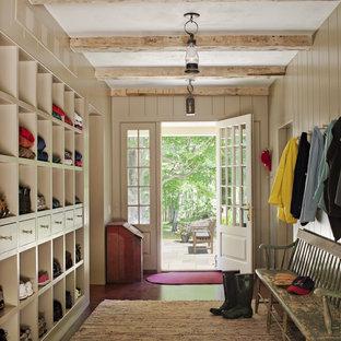 Inspiration pour une grande entrée rustique avec un vestiaire, un mur gris, une porte simple, un sol en bois brun et une porte blanche.