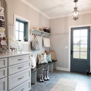 Réalisation d'une entrée champêtre de taille moyenne avec un mur beige, un sol en carrelage de porcelaine, un sol gris, un vestiaire, une porte simple et une porte grise.