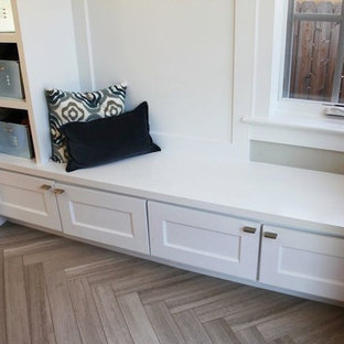 Inspiration for a small contemporary limestone floor and brown floor mudroom remodel in Denver with gray walls
