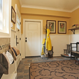 Cottage dark wood floor entryway photo in New York with yellow walls and a white front door