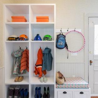 Klassisk inredning av ett mellanstort kapprum, med beige väggar, heltäckningsmatta, en enkeldörr, en vit dörr och orange golv