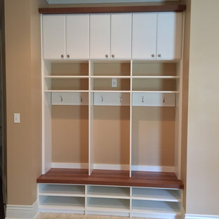 Inspiration for a mid-sized contemporary ceramic floor mudroom remodel in Other with beige walls