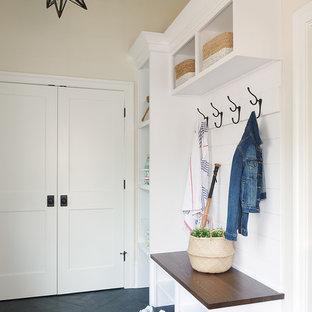 Diseño de vestíbulo posterior costero con paredes beige, suelo negro y suelo de baldosas de porcelana