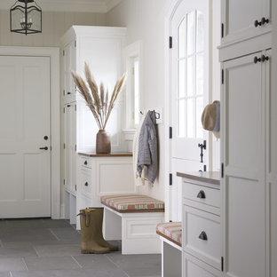 Bild på ett stort lantligt kapprum, med vita väggar, skiffergolv, en tvådelad stalldörr, en vit dörr och grått golv