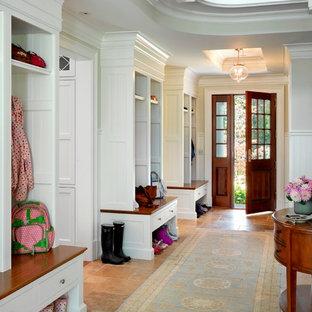 Aménagement d'une grande entrée classique avec un vestiaire, un mur blanc et une porte en bois foncé.
