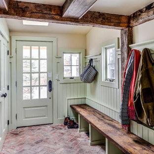 Aménagement d'une entrée classique avec un vestiaire, un mur vert, un sol en brique, une porte simple et une porte verte.