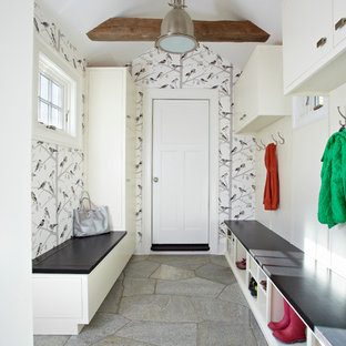 Example of a transitional gray floor mudroom design in New York with a white front door