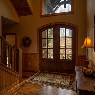 Ejemplo de distribuidor rural, grande, con paredes amarillas, suelo de madera en tonos medios, puerta doble y puerta de madera en tonos medios