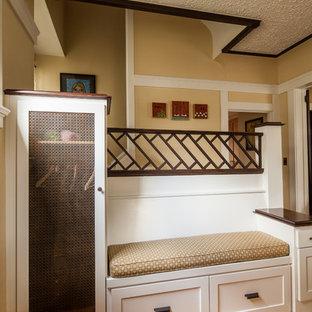 Inspiration för mellanstora amerikanska entréer, med gula väggar och mellanmörkt trägolv