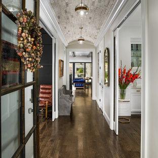 Aménagement d'une entrée classique avec un couloir, un mur gris, un sol en bois foncé, une porte simple, une porte en verre, un sol marron et un plafond voûté.