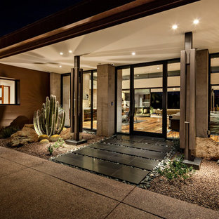 Inspiration for a southwestern black floor entryway remodel in Phoenix with gray walls and a glass front door