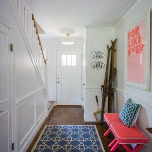 Exemple d'un hall d'entrée chic avec un mur blanc, un sol en bois brun, une porte simple et une porte blanche.