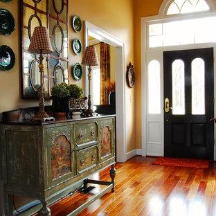 На фото: фойе с желтыми стенами, паркетным полом среднего тона, одностворчатой входной дверью и черной входной дверью с