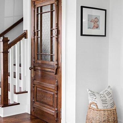 Foyer - cottage dark wood floor and brown floor foyer idea in Nashville with white walls