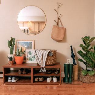 Bild på en eklektisk entré, med beige väggar, mellanmörkt trägolv och brunt golv