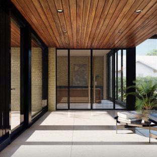 他の地域のモダンスタイルのおしゃれな玄関ロビー (磁器タイルの床、グレーの床、板張り天井、レンガ壁) の写真