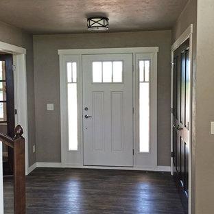 ミルウォーキーの中サイズの片開きドアトラディショナルスタイルのおしゃれな玄関ロビー (ベージュの壁、クッションフロア、白いドア) の写真