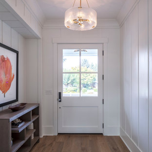 Example of a small cottage light wood floor and beige floor entryway design in San Francisco with white walls and a white front door