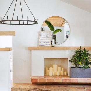 Idées déco pour un hall d'entrée méditerranéen de taille moyenne avec un mur blanc, un sol en carreau de terre cuite, une porte simple, une porte marron et un sol orange.