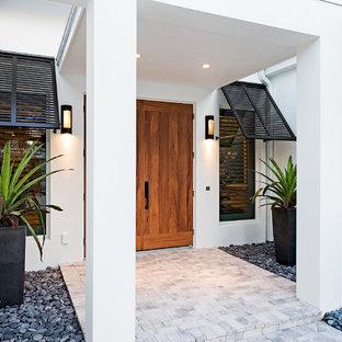 Immagine di una grande porta d'ingresso tropicale con una porta a due ante, pareti bianche e pavimento in cemento