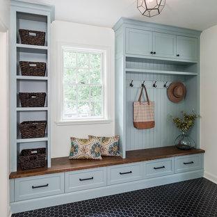 Inspiration pour une entrée traditionnelle de taille moyenne avec un vestiaire, un mur blanc, un sol en carrelage de porcelaine et un sol noir.