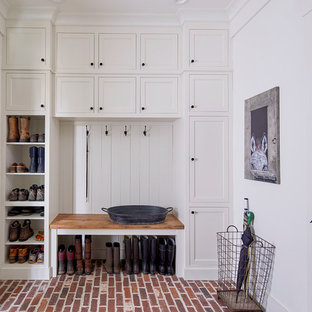 Inspiration for a farmhouse brick floor and red floor entryway remodel in Atlanta with white walls and a white front door
