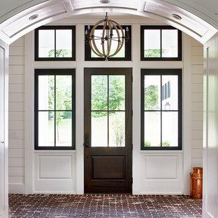 Inredning av en lantlig mellanstor ingång och ytterdörr, med vita väggar, tegelgolv, en enkeldörr, glasdörr och rött golv