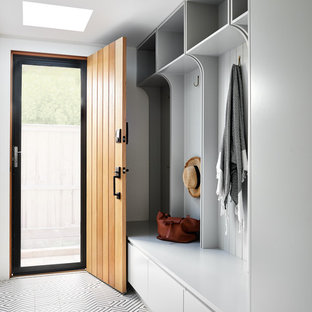 Photo of a large contemporary mudroom in Sydney with porcelain floors, white walls, a single front door, a medium wood front door and multi-coloured floor.