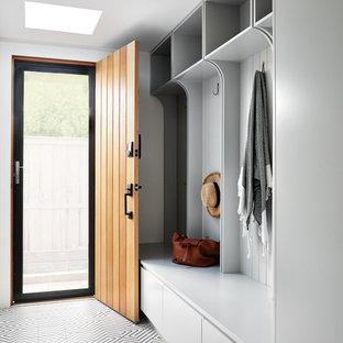 Inspiration för ett stort funkis kapprum, med klinkergolv i porslin, vita väggar, en enkeldörr, mellanmörk trädörr och flerfärgat golv