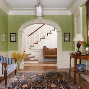 Example of a large ornate medium tone wood floor foyer design in New York with green walls