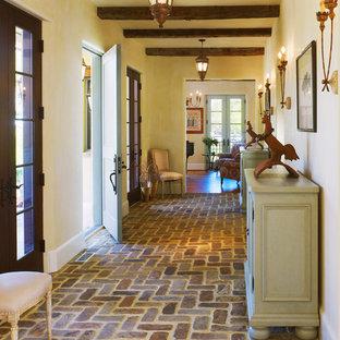 Inredning av en foajé, med tegelgolv, gula väggar, en enkeldörr och en blå dörr