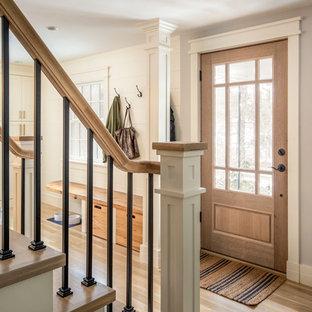 Imagen de distribuidor tradicional renovado, de tamaño medio, con paredes grises, suelo de madera clara, puerta simple y puerta de madera en tonos medios