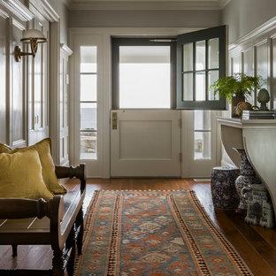 Ispirazione per un ingresso stile marinaro con pareti grigie, pavimento in legno massello medio e una porta olandese